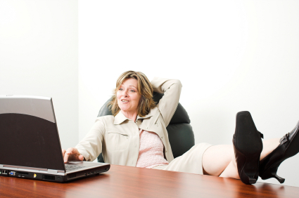 Woman sitting back with feet on desk